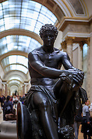 a large, black statue of a semi-nude male on display at The Louvre Museum, Paris, France