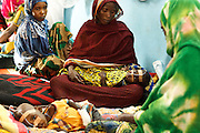 Women sit with their children, who suffer from acute malnutrition, at the UNICEF-sponsored Mao therapeutic feeding center in the town of Mao, Kanem region, Chad on Monday February 13, 2012.