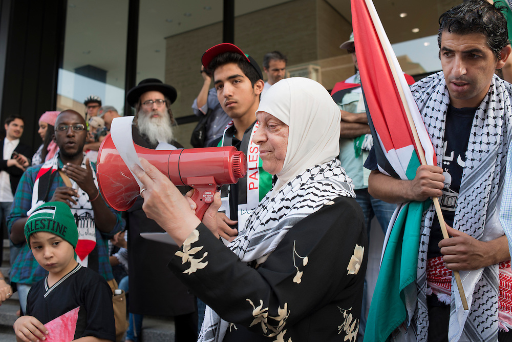 During a vigil held in Montreal in solidarity with the people of Gaza, a woman read the names of people who were killed since july 8.