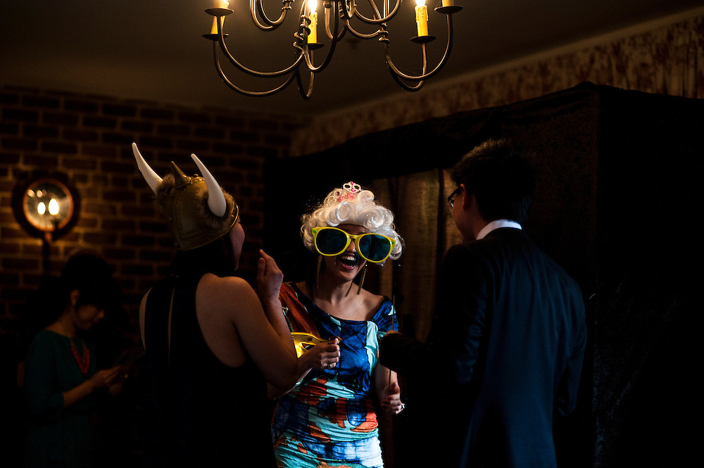 Photo by Matt Roth.Assignment ID: 30140754A..Wedding-goers at Evelyn Hsieh and Michael Wong's wedding put on silly hats and accessories before entering the photo booth during the couple's wedding reception at the the Mount Vernon Inn, in Mount Vernon, Virginia on Saturday, April 06, 2013.