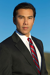 good looking Asian American man in a suit outdoors