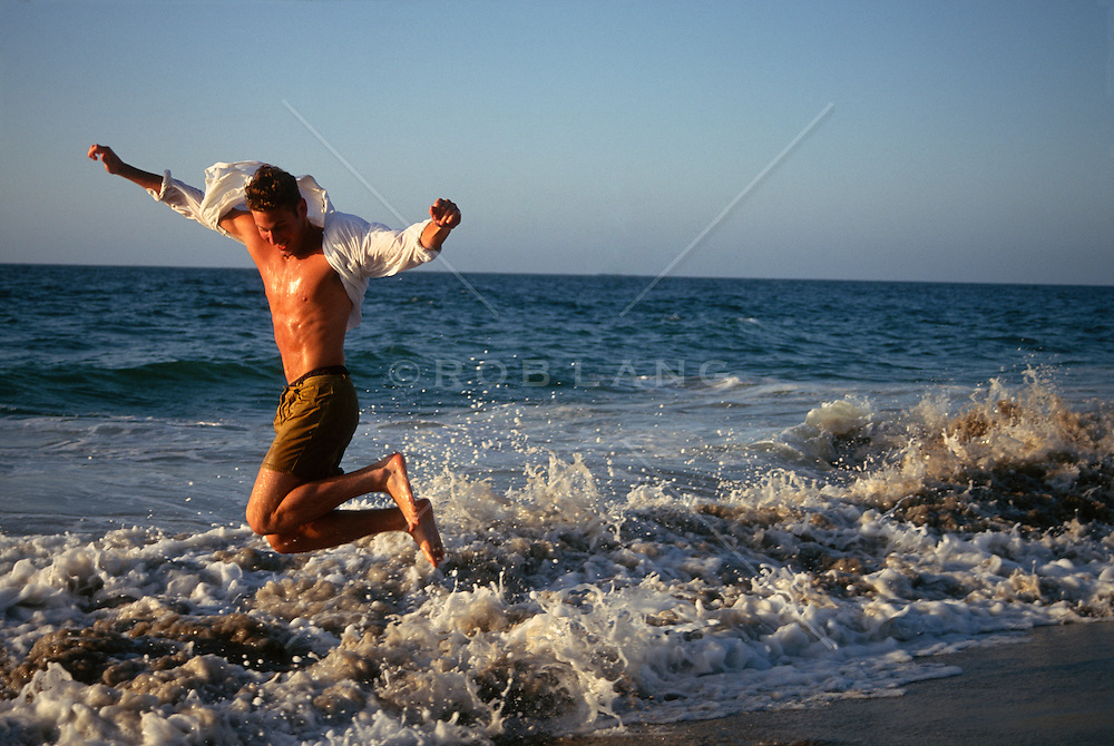 Man wearing an open shirt  jumping in the waves