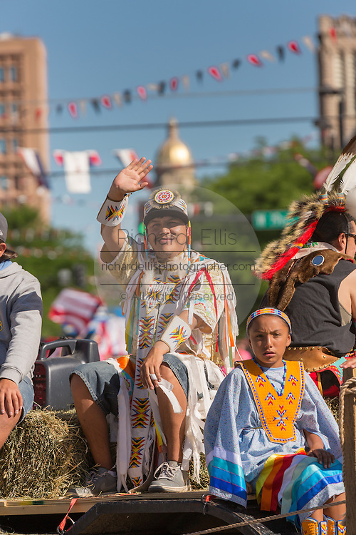 Native American Indians wave during the Cheyenne Frontier Days parade past the state capital building July 23, 2015 in Cheyenne, Wyoming. Frontier Days celebrates the cowboy traditions of the west with a rodeo, parade and fair.