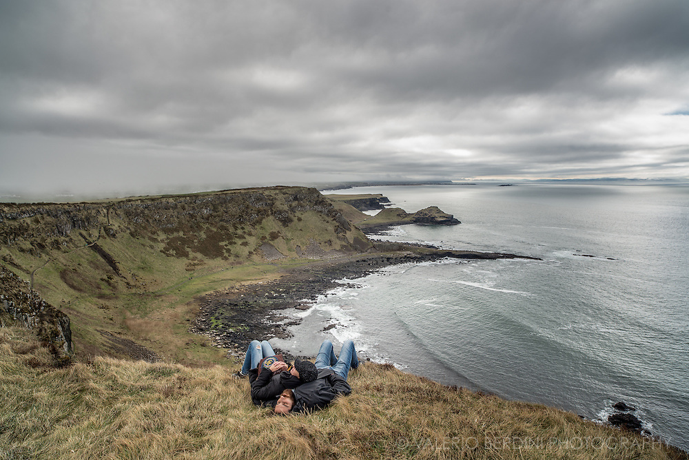 A couple enjoys the breeze and the vast landscape of the Irish coast laying on the softest grass.