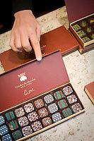 """24 October, 2008. New York, NY. Owner Namhee Girerd Kim, 53, shows a box of bon bons to the photographer at the boutique """"L'atelier du chocolat"""" . The chocolates are made by her husband, Eric Girerd.<br /> NOTE: Since no customers were at the shop, the subject posed for the photographer.<br /> <br /> ©2008 Gianni Cipriano for The New York Times<br /> cell. +1 646 465 2168 (USA)<br /> cell. +1 328 567 7923 (Italy)<br /> gianni@giannicipriano.com<br /> www.giannicipriano.com"""
