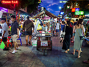 24 JULY 2018 - BANGKOK, THAILAND:  A coffee vender pushes his cart up Khao San Road in Bangkok. Khao San Road is Bangkok's original backpacker district and is still a popular hub for travelers, with an active night market and many street food stalls. The Bangkok municipal government plans to shut down the street market by early August because city officials say the venders, who set up on sidewalks and public streets, pose a threat to public safety and could impede emergency vehicles. It's the latest in a series of night markets and street markets the city has closed.  PHOTO BY JACK KURTZ