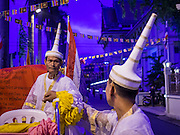 30 OCTOBER 2014 - BANGKOK, THAILAND: Brahmin priests chat before the parade marking the start of the annual temple fair at Wat Saket. Wat Saket is on a man-made hill in the historic section of Bangkok. The temple has golden spire that is 260 feet high which was the highest point in Bangkok for more than 100 years. The temple construction began in the 1800s in the reign of King Rama III and was completed in the reign of King Rama IV. The annual temple fair is held on the 12th lunar month, for nine days around the November full moon. During the fair a red cloth (reminiscent of a monk's robe) is placed around the Golden Mount while the temple grounds hosts Thai traditional theatre, food stalls and traditional shows.   PHOTO BY JACK KURTZ
