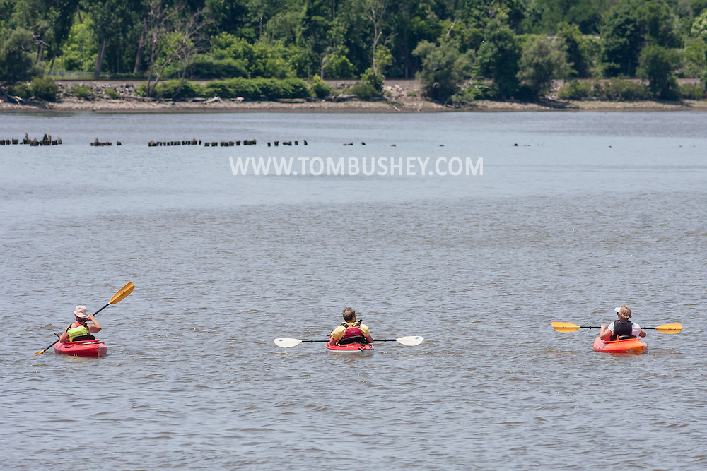 Cornwall-on-Hudson, New York - Three people paddle kayaks on Hudson River on June 20, 2014. ©Tom Bushey / The Image Works