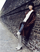 Young woman leaning against brick wall.