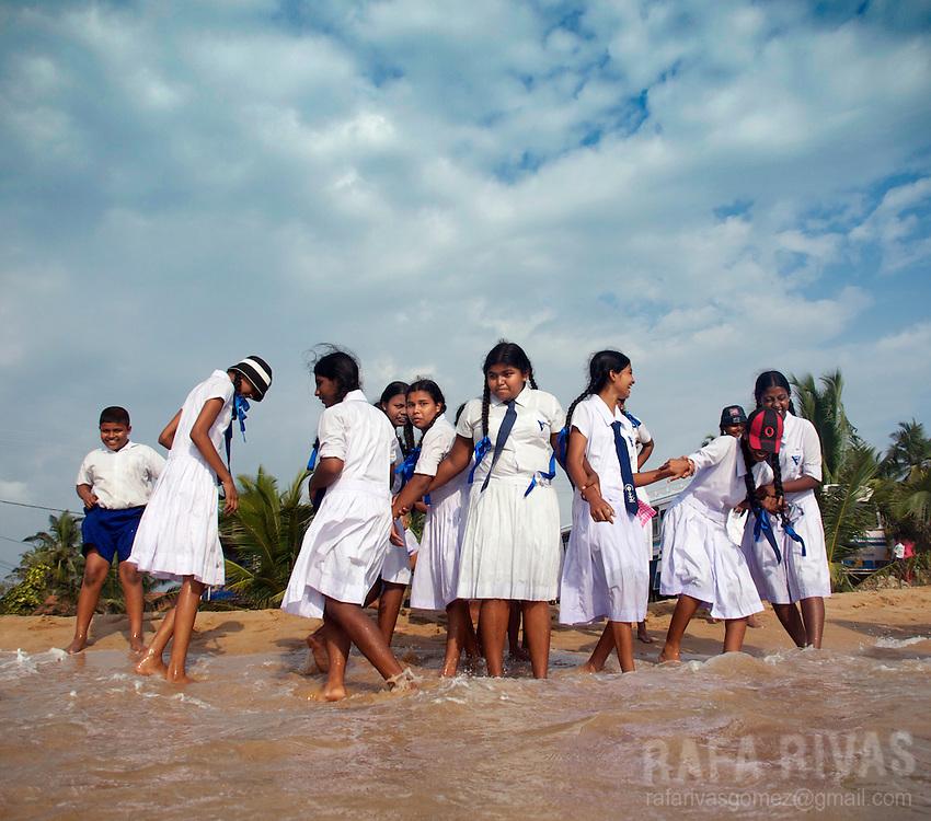 Schoolboys and girls play in a beach in Hikkaduwa, Sri Lanka, on February 24, 2011.