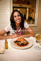 Owner Stacey Sosa  with one of Estancia 460's dishes, a plate of Salmon with Pomegranate Orange Glaze and Frizzled Leeks. Shot at the restaurant on May 25th, 2007..Photo Credit; Rahav Segev/Photopass