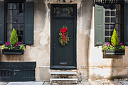 A black wooden door on a historic home decorated with a Christmas wreath on Tradd Street in Charleston, SC.
