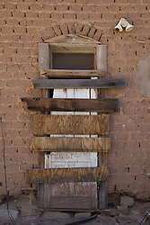 boarded up abandoned doorway on an adobe building in New Mexico
