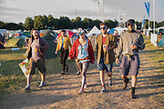 Guests dressed up and heading out of the campsite to enjoy the final night in the Arena - The 2016 Latitude Festival, Henham Park, Suffolk.