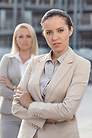 Portrait of confident young businesswoman with female colleague in background