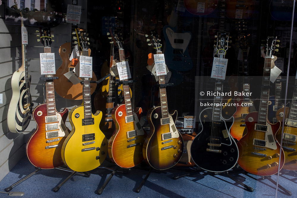 Electric Gibson guitars in Sunburst and other colours in a music shop window on London's Charing Cross Road.