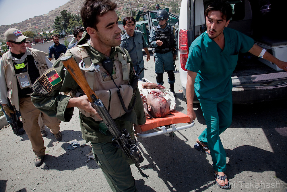 An injured person is carried to ambulance in front of the British Council compound in Kabul, Afghanistan on Aug 19, 2011 as Afghan and British forces fight against gunmen inside. Allegedly five terrorists including suicide bombers attacked the compound, killing at least 10. .(Photo by Kuni Takahashi)