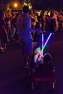 Garden City, New York, U.S. - June 6, 2014 - As night arrives, a young girl and boy hold colorful glowing sticks as they are pulled in a small red wagon at the Garden City Belmont Stakes Festival, celebrating the 146th running of Belmont Stakes at nearby Elmont the next day. There was street festival family fun with live bands, food, pony rides and more, and a main sponsor of this Long Island night event was The New York Racing Association Inc.