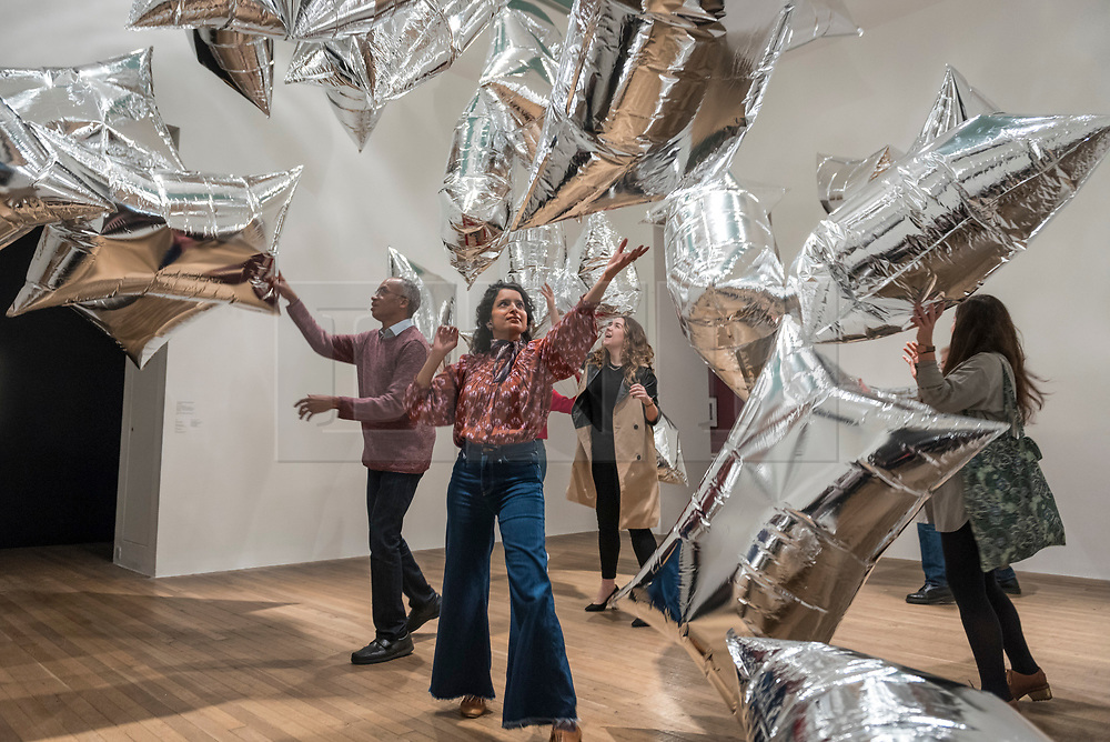 """© Licensed to London News Pictures. 10/03/2020. LONDON, UK. Staff members experience """"Silver Clouds (Warhol Museum Series)"""", 1966 , by Andy Warhol. Preview of """"Andy Warhol"""", a retrospective of over 100 works by one of the most recognisable artists of the late 20th century.  The exhibition runs 12 March to 6 September 2020 at Tate Modern.  Photo credit: Stephen Chung/LNP"""