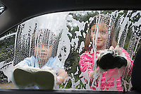 Boy and girl (7-9) washing car together view from inside car