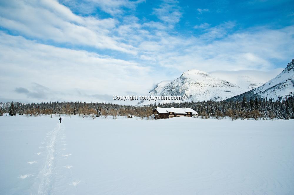 skiier sking across frozen lake in glacier national park, snow storm, cold winter skiing, glacier national park, montana