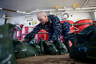 HMC Christian Elliott soaks the uniforms of sailors on board the USNS Comfort, a naval hospital ship, in permethrin to repel mosquitos - and prevent malaria - before landing to help survivors of the earthquake in Haiti on Monday, January 18, 2010 in the Atlantic Ocean off the coast of the United States.