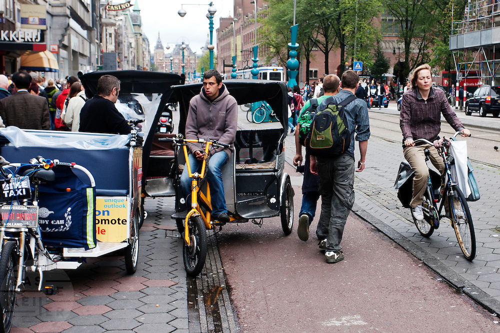 Een fietser moet op het Damrak in Amsterdam uitwijken voor een fietstaxi die op het fietspad staat en voetgangers. <br /> <br /> A cyclist has to find her way at the bike lane that is occupied by a parked bike cab and pedestrians.