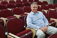 Man sitting in auditorium chair, portrait, elevated view
