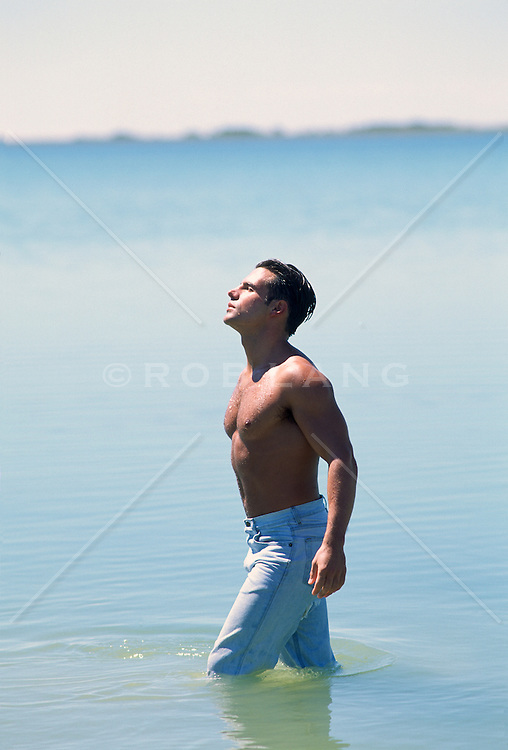 Man with no shirt and jeans in a calm lake enjoying the sun
