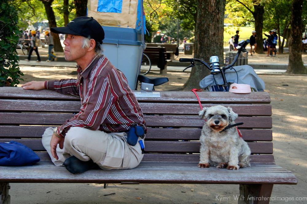 Asia, Japan, Hiroshima. Man and dog with attitudes on bench.