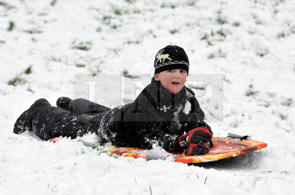 © Licensed to London News Pictures. 18/01/2013. Bristol, UK. Heavy snow provides a winter playground for Milo Lucas to enjoy sledging and tobogganing at Brandon Hill in central Bristol. 18 January 2013..Photo credit : Simon Chapman/LNP