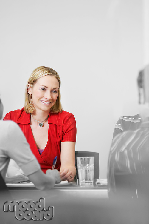Office worker sitting with colleagues at conference table (isolated colour)