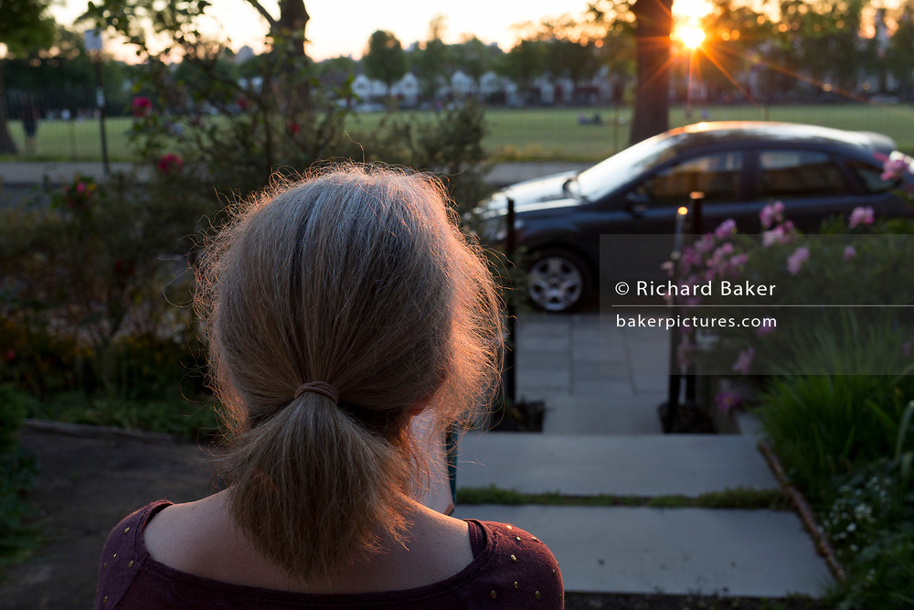 The number of UK deaths from Coronavirus, a further 363 victims taking the total to 35,704, coincided with the hottest day of the year so far, with 27.8 degrees recorded at Heathrow Airport, a lady sitting on her home's porch steps looks across the road into a setting sun while still under the UK government's lockdown rules of social distancing - during a warm evening in Lambeth, south London, on 20th May 2020, in London, England.