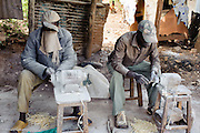 Local craftsmen grind wood and stone materials, Kibera slum, kenya