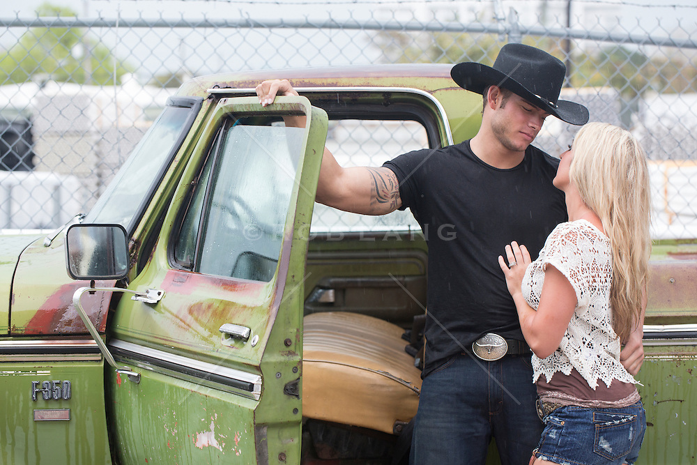 sexy cowboy looking at a blonde girl by an old pick up truck