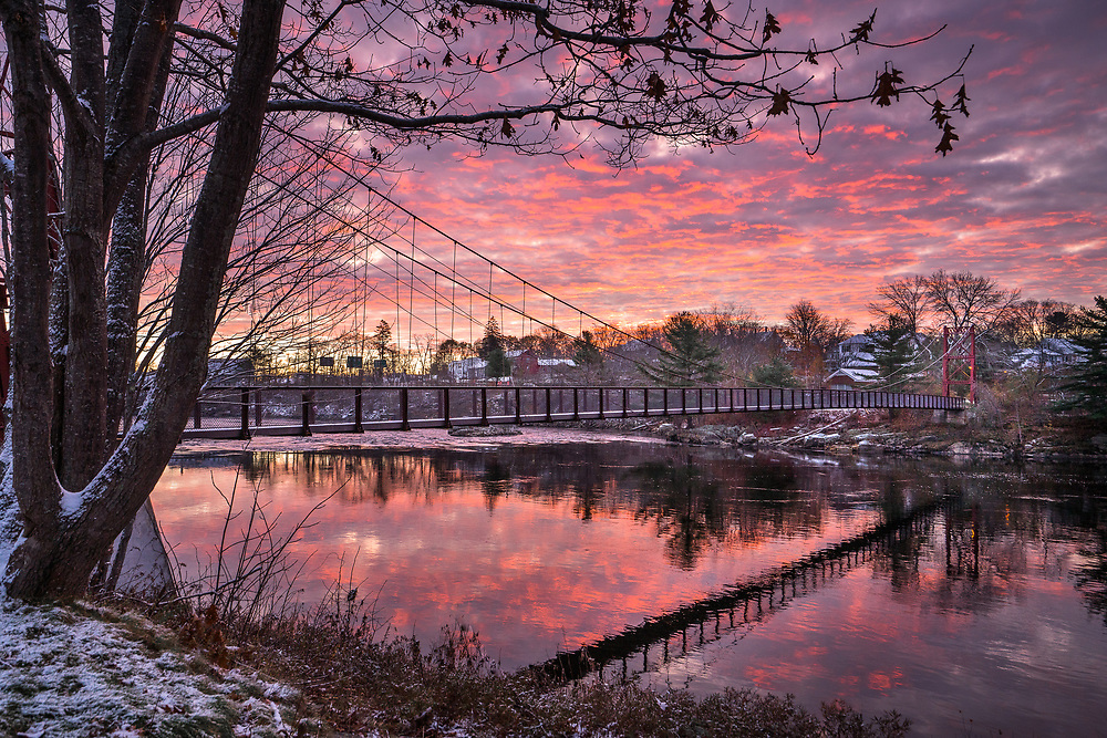 A light dusting of snow hints at the changing seasons during a beautiful sunrise near the Androscoggin Swinging Bridge connecting Brunswick and Topsham.