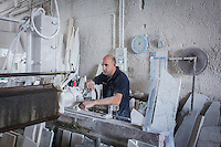 SIRACUSA, ITALY - 8 NOVEMBER 2016: Raffaele Gibilisco (35)  cuts the marble that will be used for the gravestone of Musaab Shabani, a victim of the August 24th 2014 shipwreck, here at the Gibilisco marble-worker's workshop in Siracusa, Italy, on November 8th 2016.<br /> <br /> Musaab Shabani was buried in the cemetery of Sortino, marked by a gravestone with the number nine because at the time he hadn't been identified yet. He was later identified by his brother Abd thanks to the efforts of policeman Angelo Milazzo. Since then, Abd has arranged to have a gravestone made bearing his brother's name and date and place of birth as well as a religious inscription in Arabic, bringing a final bit of closure to this tragic chapter. <br /> <br /> On August 24th 2014, a boat carrying more than 400 migrants, departed from the coasts of Libya in the attempt to reach Italy, capsized in international waters in the Mediterranean Sea. Rescuers of the Italian Navy saved 352 people, and recovered 24 lifeless bodies.<br /> <br /> Following the events of the Arab Spring in 2011, including Gaddafi's death and Libya's plunge towards chaos, clandestine crossings skyrocketed, as did the number of people drowning. In 2014 over 170,000 arrived in Italy and since then more than 10,000 perished in the Mediterranean sea.<br /> <br /> Only a fraction of these bodies have ever been recovered, and, of the ones that have, the majority remain unidentified. In Sicily alone there are more than 1,500 graves of anonymous refugees and migrants–people from Syria and other war torn countries–who have drowned in shipwrecks at sea.<br /> <br /> Despite the decades long persistence of the problem, Italy has yet to develop a comprehensive approach to handling the bodies of shipwreck victims. Many pieces of a functional body identification system are in place, but its overall effectiveness is crippled by a lack of coordination between the various local agencies involved and national authorities.