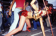 A girl in a carnival costume bending over doing a provocative dance, Notting Hill Carnival, London, UK 2003