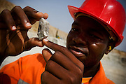 Geologist Jules To? holds a sample of ore he says contains gold in the main pit of the Youga gold mine near the town of Youga, approximately 205 km southeast of Burkina Faso's capital Ouagadougou on Tuesday April 28, 2009..
