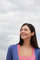 Young woman smiling standing on beach low angle view