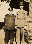 Father and son, police officer and soldier, in front of there house. 1943