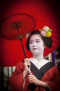 Geisha woman under red umbrella in rain watches Jidai Matsuri festival of the Ages parade Kyoto in autumn, Japan.