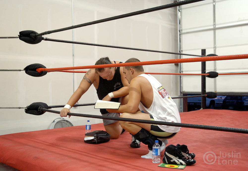Dennis Dobson (L) and WIl Ingram (R), of the Christian Wrestling Federation, read a bible during bible study following the group's regular practice in Rockwall, TX Monday, July 18, 2005. The group uses wrestling to minister to people who are interested in the sport but have not yet found Jesus. The group has been ministering since 2000.