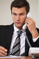 Businessman conversing on landline phone, portrait