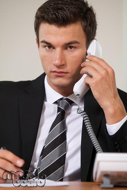 Businessman conversing on landline phone, portrait