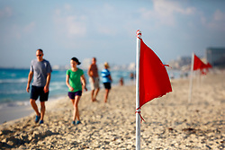 10 Feb 2014. Cancun, Mexico.<br /> Red surf flags warn of heavy surf conditions on  the tourist beach at Isla Cancun along the Zona Hotelera on the Carribean Sea. <br /> Photo; Charlie Varley/varleypix.com