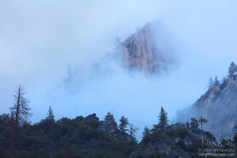Eagle Peak, a ‎7,783-foot (2,372-meter) peak that is the highest of the Three Brothers, rises above storm clouds in Yosemite National Park, California.