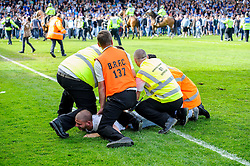 A Bristol Rovers supporter is restrained for reacting angrily after a 0-1 loss in the match to confirm their sides relegation from League 2 into the Conference division - Photo mandatory by-line: Rogan Thomson/JMP - 07966 386802 - 03/05/2014 - SPORT - FOOTBALL - Memorial Stadium, Bristol - Bristol Rovers v Mansfield Town - Sky Bet League Two. (Note: Mansfield are wearing a Rovers spare kit having forgotten their own).