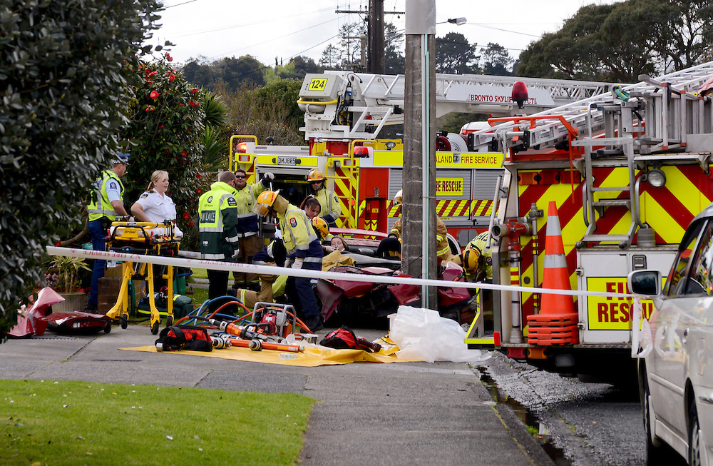 Rescue workers removing an injured woman from the wreckage of a car that hit a power pole in Mill Road, Whangarei, Northland, New Zealand, Tuesday September 10,  2013. Credit:SNPA / Malcolm Pullman