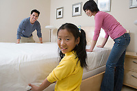 Mother, father and daughter making a bed together
